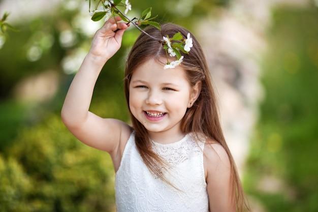 Hübsches lächelndes kleines mädchen im cremefarbenen kleid im blumengarten