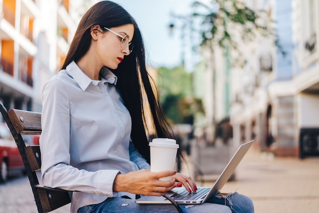 Hübsches lächelndes lässig gekleidetes studentenmädchen, das draußen auf einer bank sitzt, ihren kaffee genießt und mit laptop arbeitet