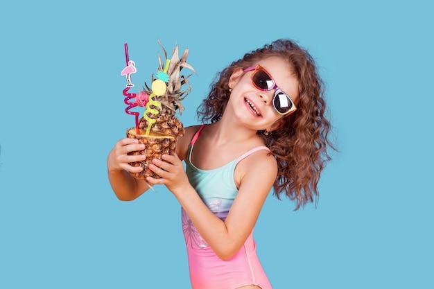 Hübsches lächelndes mädchen mit lockigem haar, das rosa und blaue badebekleidung, sonnenbrille und ananascocktail hält