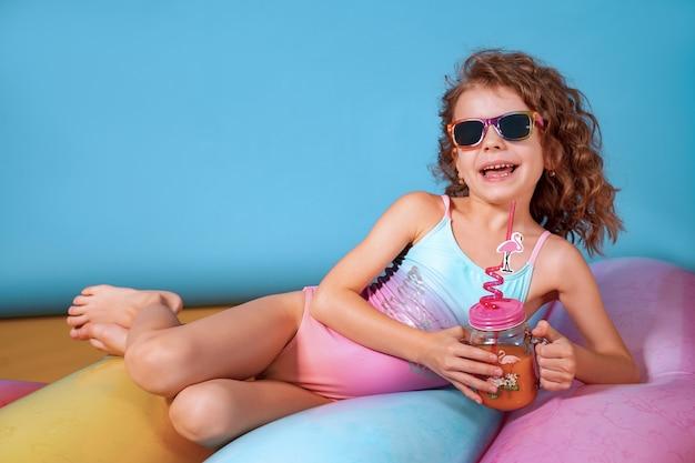 Hübsches lächelndes mädchen mit lockigem haar, das rosa und blaue badebekleidung, sonnenbrille und haltenden saft trägt