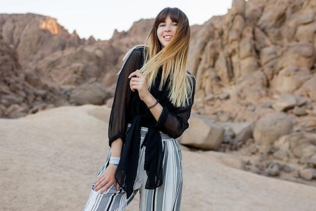 Hübsches lächelndes modisches mädchen, das in den ägyptischen wüstensanddünen aufwirft.