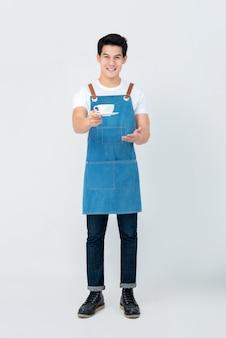 Hübsches lächelndes serviceorientiertes asiatisches mann barista, das einen tasse kaffee dient