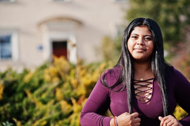 Hübsches latino xxl modellmädchen aus ecuador tragen auf violetter bluse, die an der straße gestellt wird.