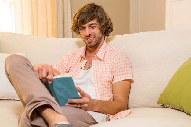 Hübsches lesen eines buches, das auf der couch im wohnzimmer sitzt
