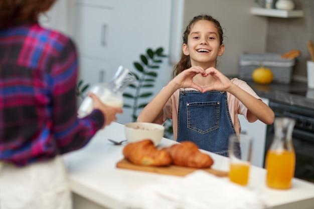Hübsches lockiges kleines mädchen, das jeans und t-shirt in der küche mit ihrer mutter trägt und die kamera lächelt, die herzsymbolform mit den händen macht, nimmt frühstück zusammen.