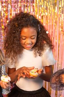 Hübsches mädchen an der festlichen partei, die cupcake hält