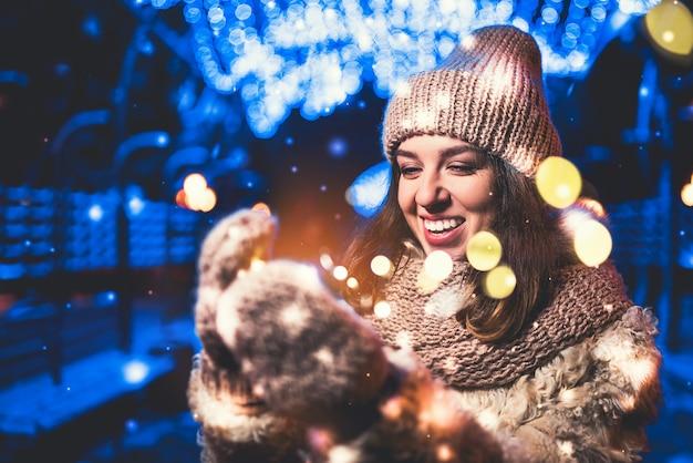Hübsches mädchen auf der straße mit weihnachtslichtern herum