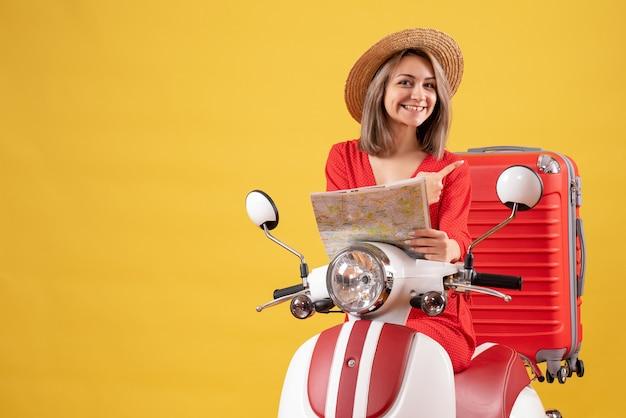 Hübsches mädchen auf moped, das eine karte hält, die auf ihren koffer zeigt