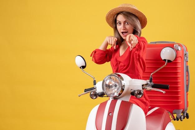 Hübsches mädchen auf moped mit rotem koffer, der auf die kamera zeigt