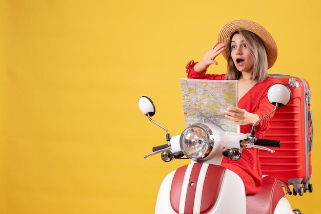 Hübsches mädchen auf moped mit rotem koffer, der eine karte hält, die jemanden begrüßt
