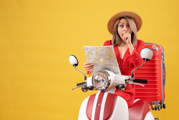 Hübsches mädchen auf moped mit rotem koffer, der eine karte hält