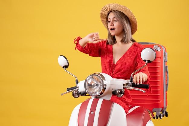 Hübsches mädchen auf moped mit rotem koffer, der zeit überprüft
