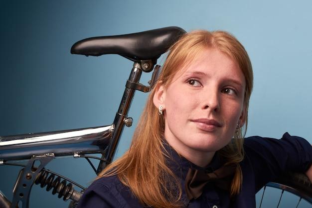Hübsches mädchen, das auf dem boden eines fahrradladens nahe einem fahrrad sitzt