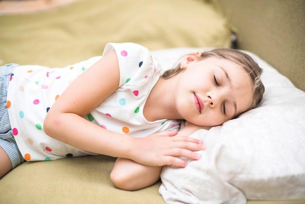 Hübsches mädchen, das auf gemütlichem bett schläft