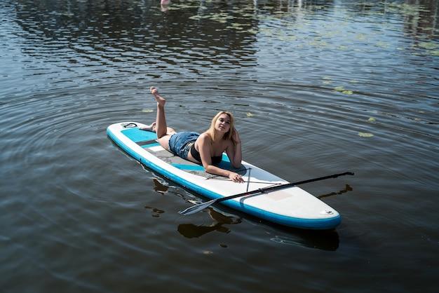 Hübsches mädchen, das auf paddelbrett auf dunkelblauem teichwasser liegt. reise- oder urlaubskonzept