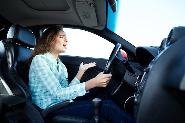 Hübsches mädchen, das blaues hemd trägt, das im neuen auto sitzt, glücklich, im verkehr stecken bleibt, musik hört, porträt, im auto singend, radiowelle.