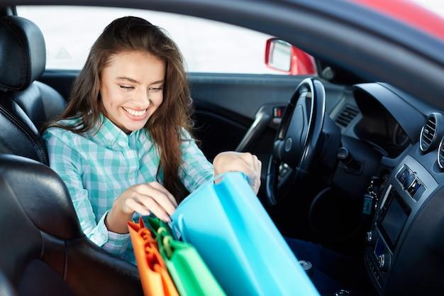 Hübsches mädchen, das blaues hemd trägt, das im neuen auto sitzt, im verkehr stecken, porträt, neues auto kauft, fahrerin, einkaufstaschen auf einem sitz, einkaufen, glücklich.