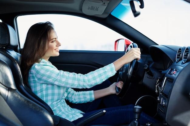 Hübsches mädchen, das blaues hemd trägt, das im neuen automobil sitzt, glücklich, im verkehr stecken bleibt, musik hört, porträt.