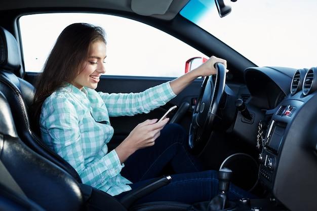 Hübsches mädchen, das blaues hemd trägt, das im neuen automobil sitzt, glücklich, im verkehr stecken bleibt, musik, porträt hört, handy hält und bildschirm betrachtet.