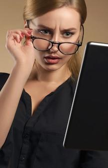 Hübsches mädchen, das brille abnimmt und die tablette mit verwirrtem gesichtsausdruck betrachtet