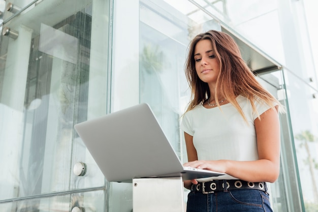 Hübsches mädchen, das das internet auf einem laptop durchstöbert