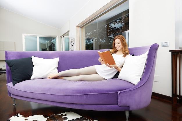 Hübsches mädchen, das ein buch auf purpurrotem sofa liest