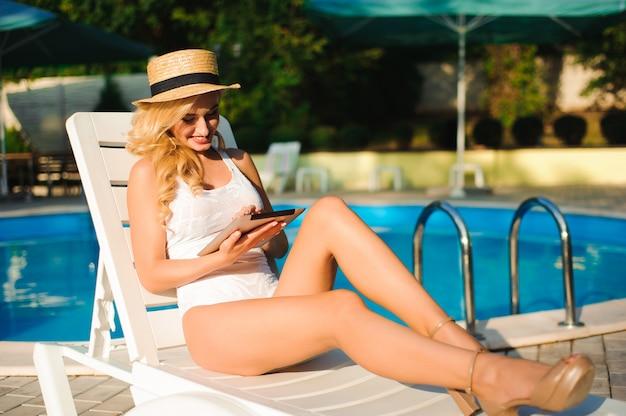 Hübsches mädchen, das ein digitales tablett verwendet und beim sonnenbaden auf der chaiselongue nahe dem pool lächelt.