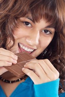 Hübsches mädchen, das eine schokoladentafel getrennt im weiß anhält