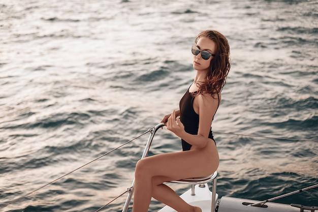 Hübsches mädchen, das einen schwarzen body und eine sonnenbrille trägt und auf ihrer yacht sitzt und vor dem hintergrund des wassers posiert.