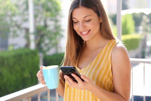 Hübsches mädchen, das frühstück auf balkon am sonnigen morgen hat. sie hält eine tasse in der hand und liest die nachrichten ihrer freunde auf dem handy.