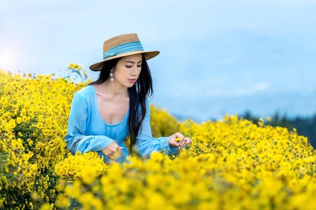 Hübsches mädchen, das im chrysanthemenfeld in chiang mai, thailand genießt Kostenlose Fotos