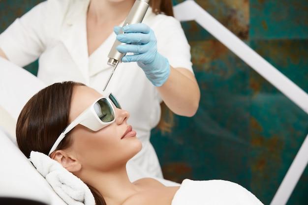 Hübsches mädchen, das im schönheitssalon liegt und lasertherapie für stirn trägt, die schutzbrille trägt