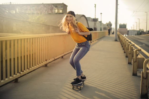 Hübsches mädchen, das in die stadt skateboard fährt