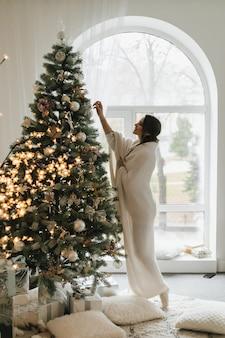 Hübsches mädchen, das in ein plaid gewickelt wird, hängt ein spielzeug an einem weihnachtsbaum