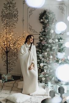 Hübsches mädchen, das in ein plaid gewickelt wird, steht nahe einem weihnachtsbaum