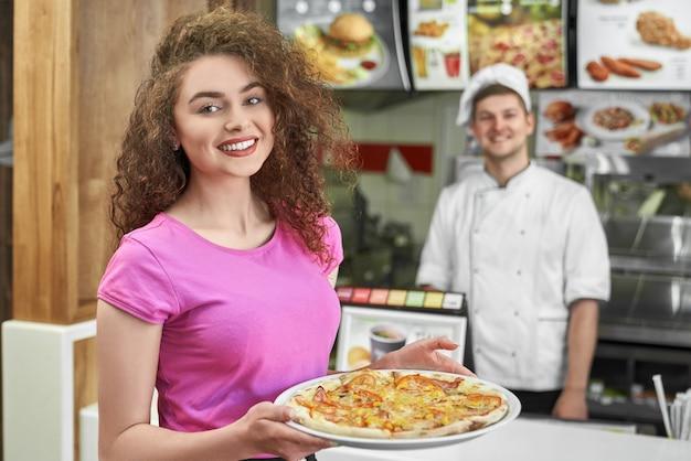 Hübsches mädchen, das köstliche pizza in der pizzeria hält.