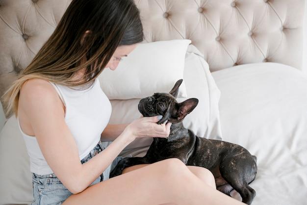 Hübsches mädchen, das mit ihrer französischen bulldogge spielt