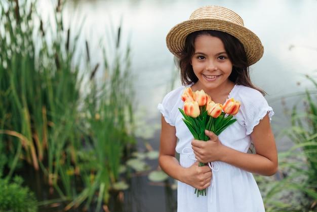 Hübsches mädchen, das mittleren schuss der tulpen hält