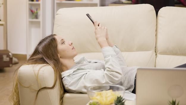 Hübsches mädchen, das sich mit ihrem smartphone auf der couch entspannt. freund im hintergrund.