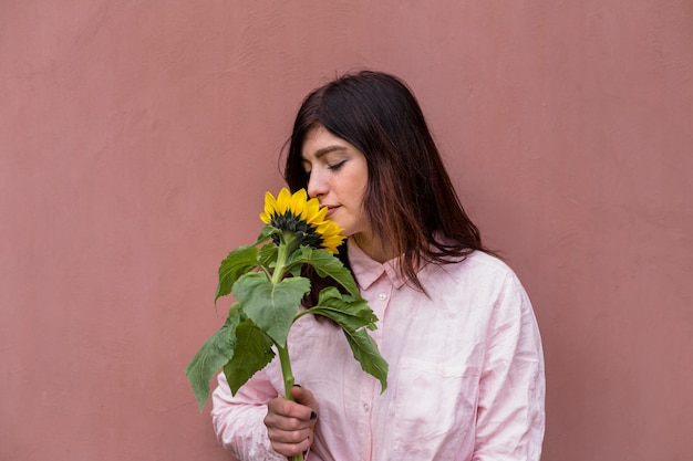 Hübsches mädchen, das sonnenblume hält