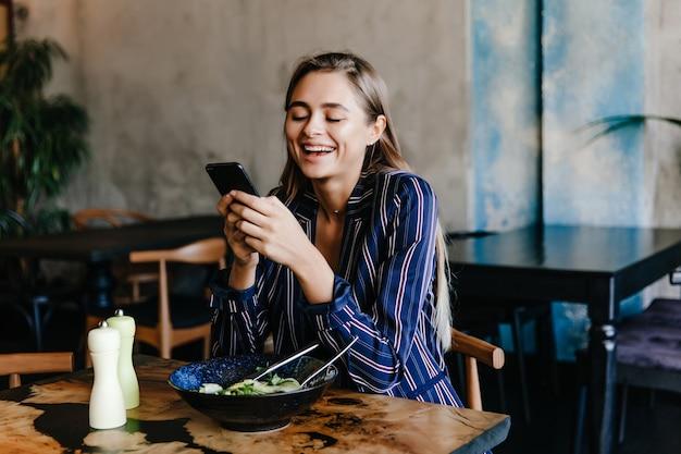 Hübsches mädchen, das telefon während des abendessens im café benutzt. porträt der glücklichen jungen frau, die gemüse isst.
