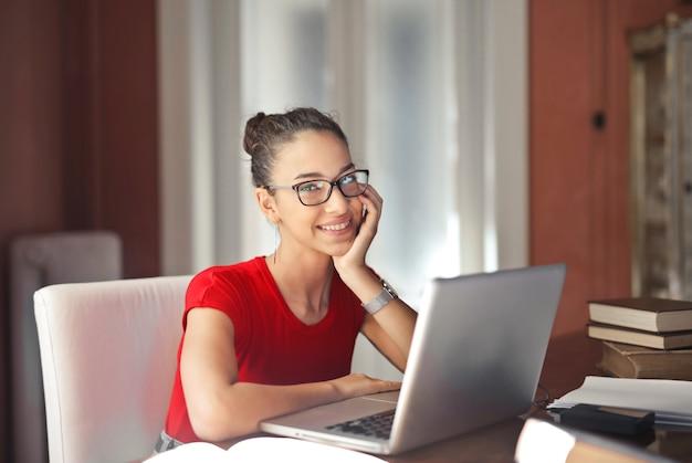 Hübsches mädchen, das über einem laptop lächelt