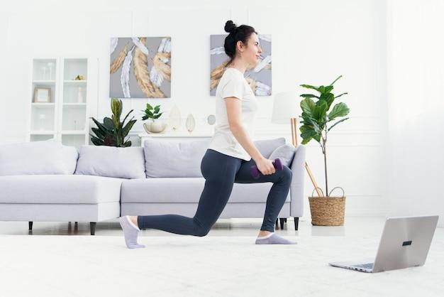 Hübsches mädchen, das yoga-tutorial auf laptop beobachtet