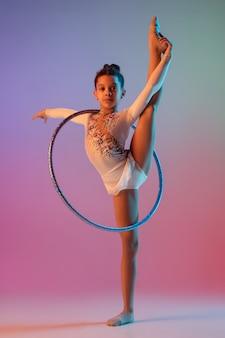 Hübsches mädchen der rhythmischen turnerin der afroamerikaner, die auf gradientenwand im neonlicht übt