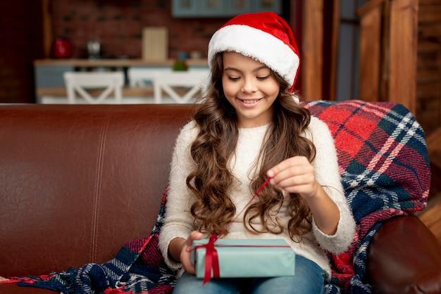 Hübsches mädchen des mittleren schusses, das ihr geschenk öffnet