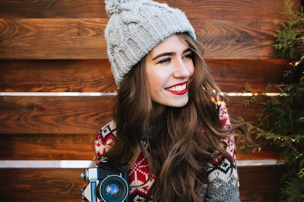 Hübsches mädchen des nahaufnahmeporträts mit langen haaren und schneeweißem lächeln im strickhut mit kamera auf holz. sie lächelt zur seite.