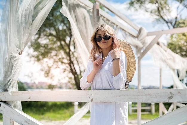 Hübsches mädchen genießen sonnigen sommertag in der nähe des sees im weißen pavillon. konzept der entspannung oder des urlaubs