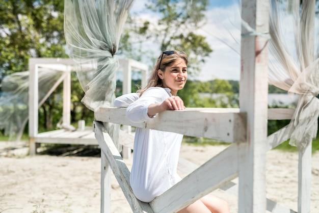 Hübsches mädchen genießen sonnigen sommertag nahe see im weißen pavillon