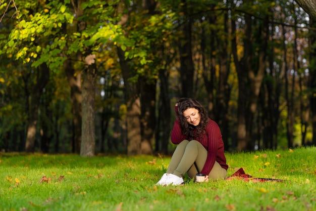 Hübsches mädchen genießt den herbst und die schönheit der natur, die auf einem grünen rasen im park sitzt. herbststimmung.