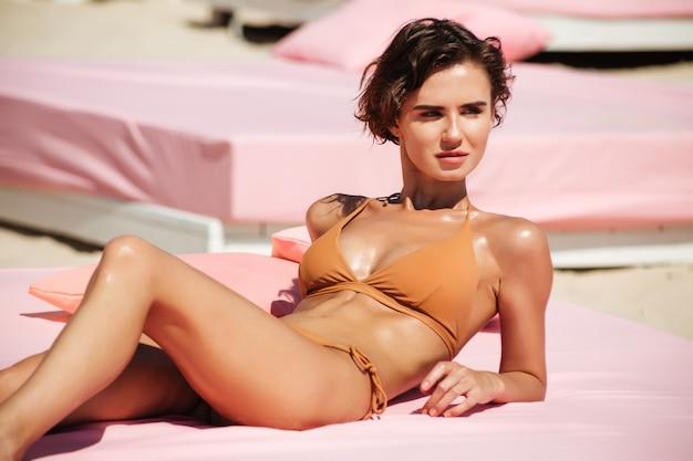 Hübsches mädchen im bikini, das auf strandbett liegt und verträumt beiseite schaut. porträt der jungen schönen dame im beige badeanzug beim sonnenbaden beim verweilen am strand